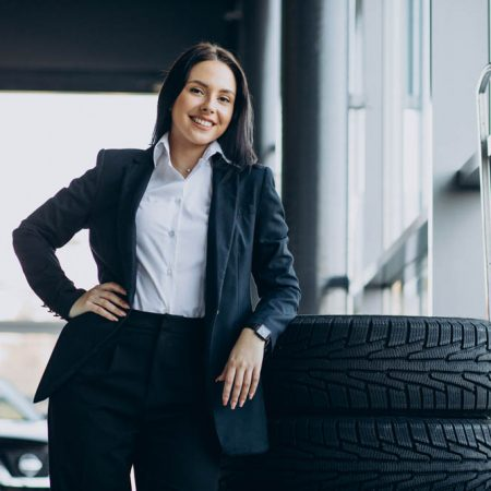 Saleswoman in car showroom selling cars